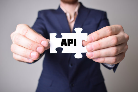 Businessman holding a puzzle with the inscription:API
