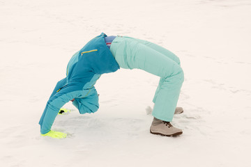 A young lady in a blue ski suit makes gymnastics in the snow. Yellow sled, sunglasses, bright clothes. Girl happy outdoors. The concept of a fun winter vacation for the whole family