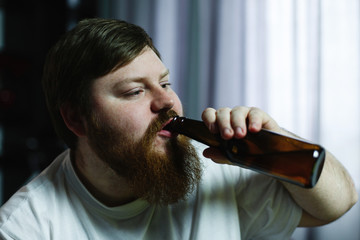 Close-up of a fat man looking ugly while he drinks beer