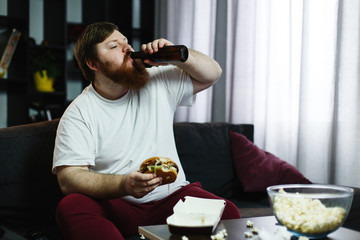 Fat man eats burger with beer sitting at the table before TV