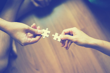 two hands trying to connect couple puzzle piece  Jigsaw alone wooden puzzle Teamwork, partnership, business idea, cooperation management concept