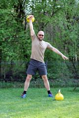 Mann macht Sport mit Kettlebell im Garten