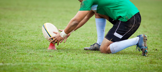 rugby player preparing to kick the oval ball during game