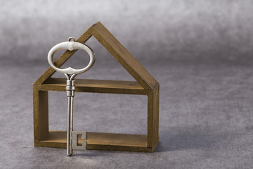 Symbol of the house with silver key on grey background