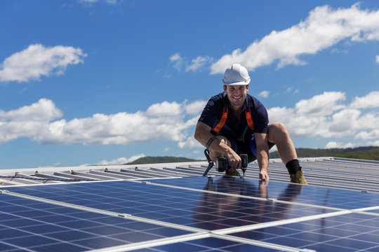 Solar panel technician with drill installing solar panels