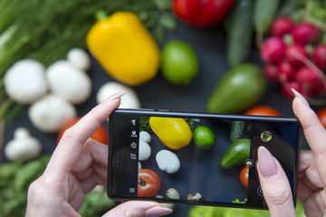 Girl taking picture of healthy food with her smartphone. Vegan food concept. Top view.