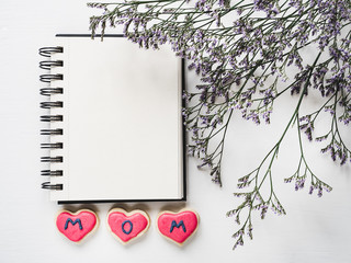 Heart-shaped cookie with the word MOM, covered with glaze, sketchbook with a blank page for your inscription and a beautiful branch of flowers. White, isolated background. Top view