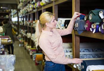 Woman choosing textiles in shop