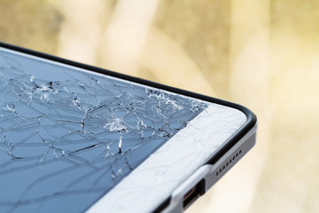 Smartphone with broken screen. Damaged phone glass. Closeup, yellow background, selective focus