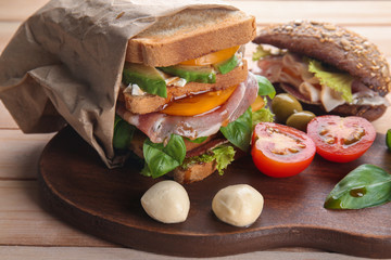 Tasty homemade sandwiches on wooden board