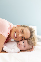 young, beautiful and blond mother with pink shirt is cuddling with her baby in bed
