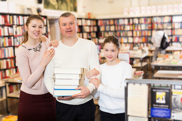 parents and girl standing with stack of books