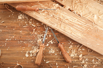 Chisels, wooden boards and sawdust in carpenter's workshop