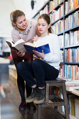 Girl choosing interesting book with mother