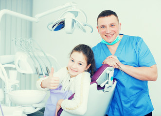 Male dentist with satisfied girl
