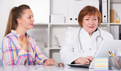 Portrait of mature medical worker talking with patient