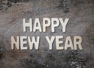 'Happy New Year' wording made of wooden letters arranged on weathered old wooden table.