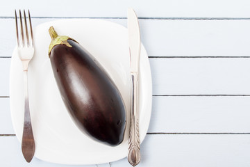 One whole eggplant on white plate. Fresh organic fruit. Healthy nutrition concept