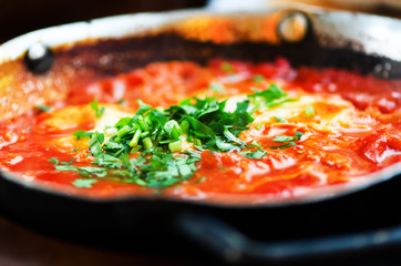 Shakshuka. Traditional jewish food and middle eastern cuisine recipe. Fried eggs, tomatoes, bell pepper and parsley in a pan. Close up, selective focus. Homemade breakfast