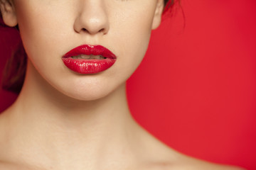 red glossy lipstick on red background