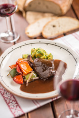 Confit rabbit leg with vegetable bread redvine in pub or restaurant