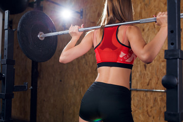 Photo from back of sports woman crouching with bar