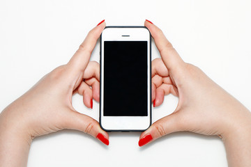 The girl is holding a white phone in her hand with red nails.
