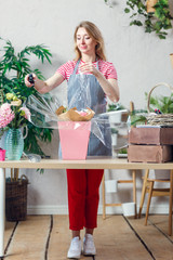 Photo of florist woman with stapler decorating flower arrangement at table with flowers, boxes