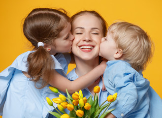 concept of mother's day. mom and children with flower on colored background.
