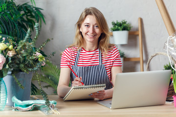 Picture of smiling florist woman with notepad at table with laptop