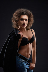 Sexy woman posing in black bra and blue jeans. keeping black jacket .Looking beatiful,confident, charismatic. Having pretty face features, many little curles and day make up. Studio black background.