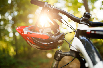 Photo of bicycle with helmet on steering wheel on blurred background