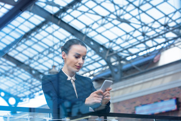 beautiful businesswoman leaning on railing and using smartphone