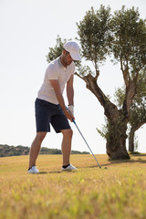 Golfer outside the golf course with club