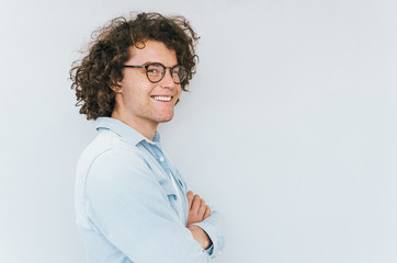 Profile horizontal view portrait of handsome young male with curly hair, wearing denim blue shirt and round trendy spectacles, looking to the camera. Copy space for advertisement. People race concept.