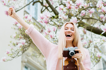Excited emotional portrait of blond woman photographer enjoying great picture and holding hand aside under blooming magnolia tree background. Tourism, travel and new fresh impression concept.