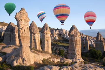 Colorful hot air balloons flying over Love valley in Cappadocia, Anatolia, Turkey