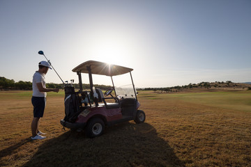 Golfer choosing club from golf cart