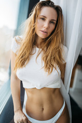 Sexy female underwear model. Young fit woman with white cotton t-shirt and panties. standing at the window