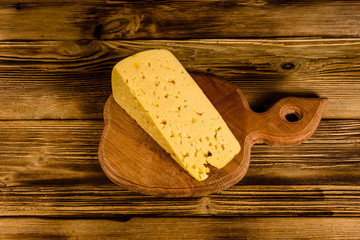Cutting board with piece of cheese on a wooden table