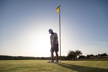 Golf player near flag pole hole at sunset