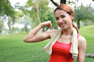 Healthy strong Asian woman in red sportswear showing her hands in natural park. Fitness and lifestyle concept.