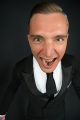 Happy man with blond hair in black suit. Ballroom dancer shout in stylish tuxedo. Businessman or groom with excited face and open mouth. Fashion style and trend