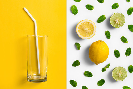 Empty glass on split colored background, yellow and white with mint leaves ,lemon and lime arrangement.
