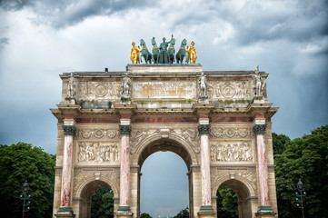 Arc de triomphe du carrousel in paris, france. Arch monument and green trees on cloudy sky. Architectural symbol of peace victory and fame. Vacation and wanderlust in french capital