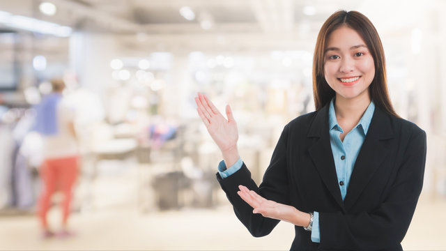 Portrait of Asian beautiful smiling businesswoman customer support on blurred interior shopping mall background and copy space.Concept business job service.