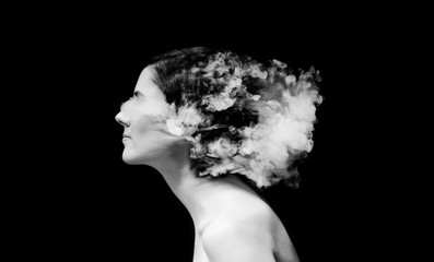 creative of art woman portrait and smoke in face. black in white portrait and smoke on black background.