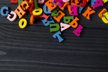 Multicolor letters on a dark blue wooden  background. Colorful wooden alphabet on a table.