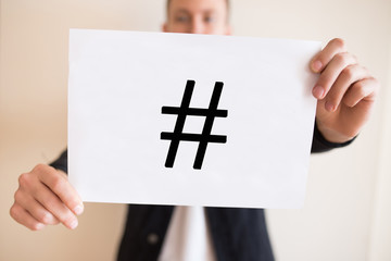 A guy holding a sheet of paper with a hashtag symbol