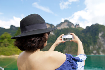 Back view of woman  Wearing stylish blue dress and stylish hat.   taking pictures of in Khao Sok lake or sea.